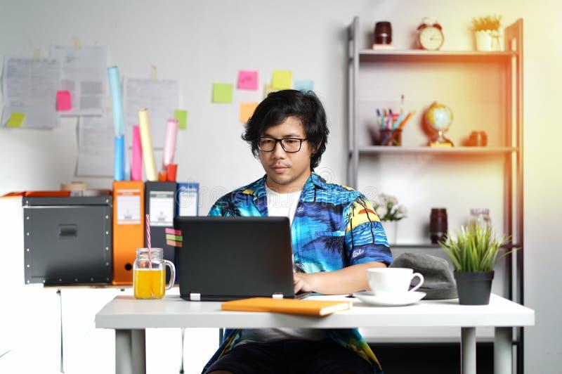 年轻人与在暑假季节的膝上型计算机一起使用在Offic 免版税图库摄影