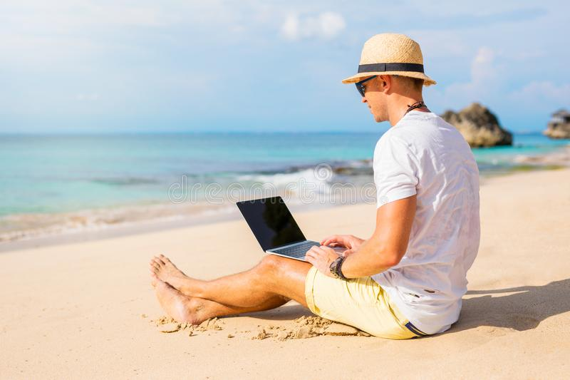 年轻人与在海滩的便携式计算机一起使用 免版税库存照片
