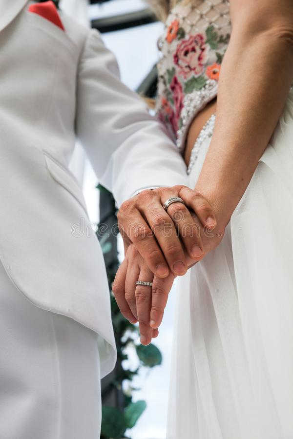 年轻人与握手,仪式婚礼之日的夫妇结婚 免版税图库摄影