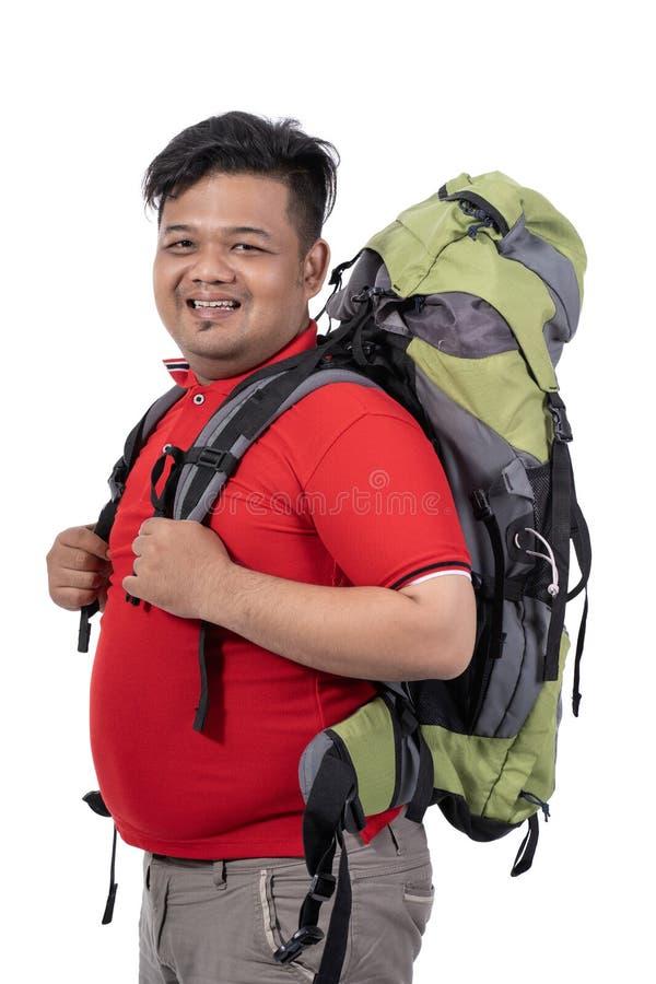 年轻人与背包的徒步旅行者微笑画象  免版税图库摄影