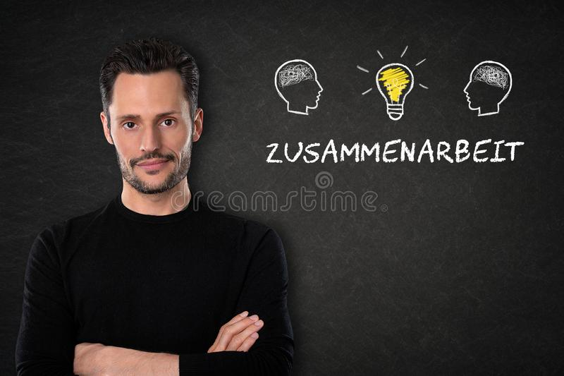 年轻人与& x27;Zusammenarbeit& x27;文本、头有脑子的和轻的电灯泡想法在黑板背景 翻译: 图库摄影