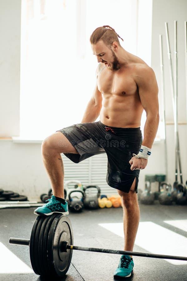 年轻人为在健身房的杠铃训练做准备 把他的腿放在杠铃上 库存照片