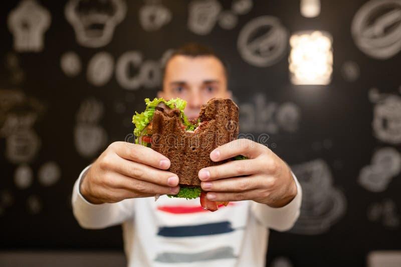 年轻人举行被咬住的三明治特写镜头滑稽的被弄脏的protrait由他的两只手的 三明治在焦点 可能 免版税库存照片