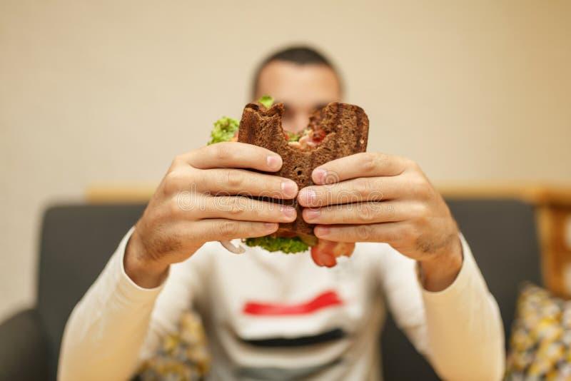 年轻人举行被咬住的三明治特写镜头滑稽的被弄脏的protrait由他的两只手的 三明治在焦点 r 库存照片