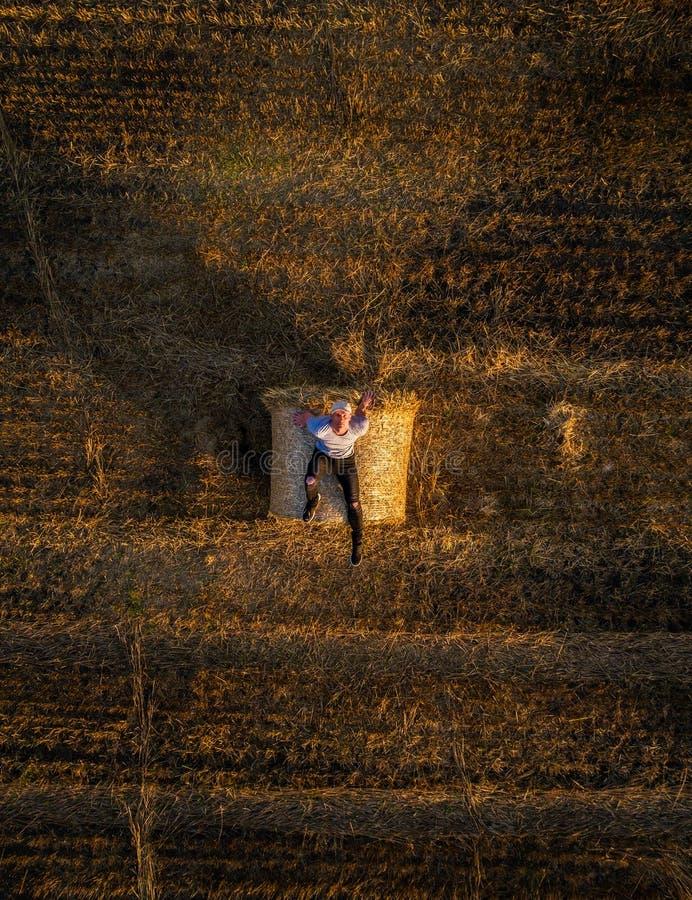年轻人享受日落在干草捆顶部 免版税库存图片