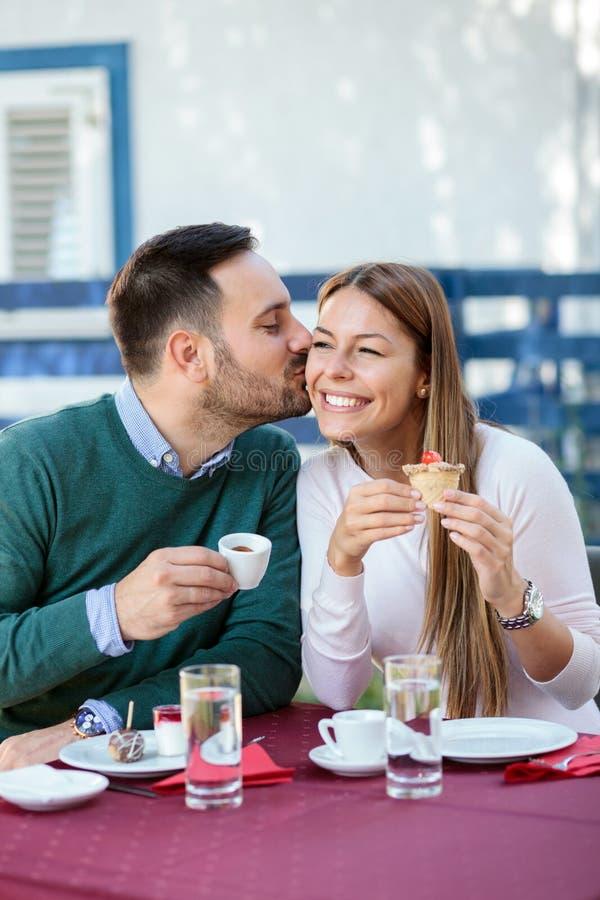 年轻人亲吻他的面颊的女朋友,喝在咖啡馆的咖啡 免版税库存图片