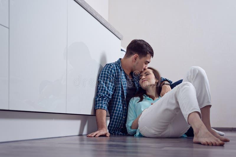 年轻人亲吻的妇女前额坐地板在白色厨房,关系,家庭,爱,乔迁庆宴里 免版税库存图片