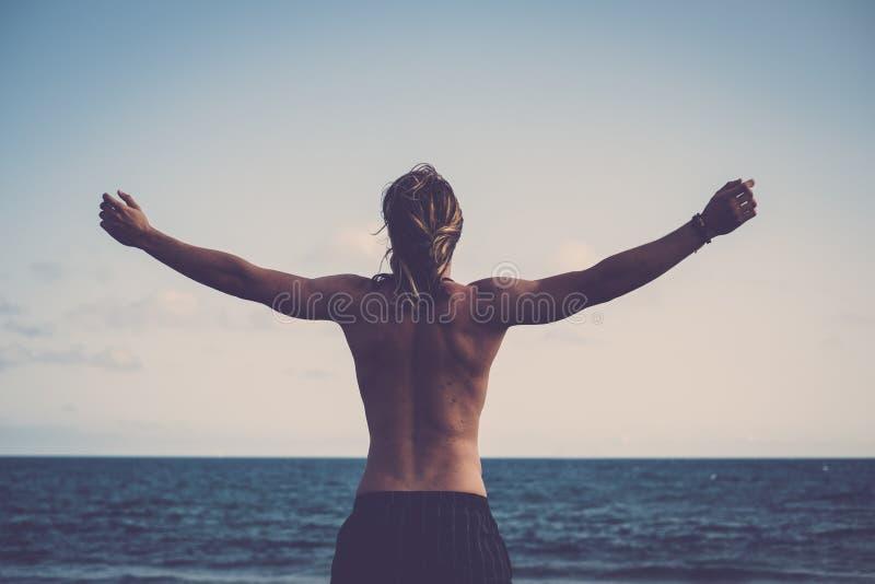 年轻人从后方打开的胳膊观看了并且拥抱在享受自由和假期的他前面的水海洋天堂 库存图片