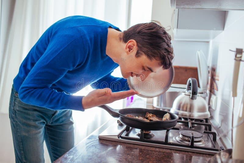年轻人从平底锅的嗅食物在厨房 免版税库存图片