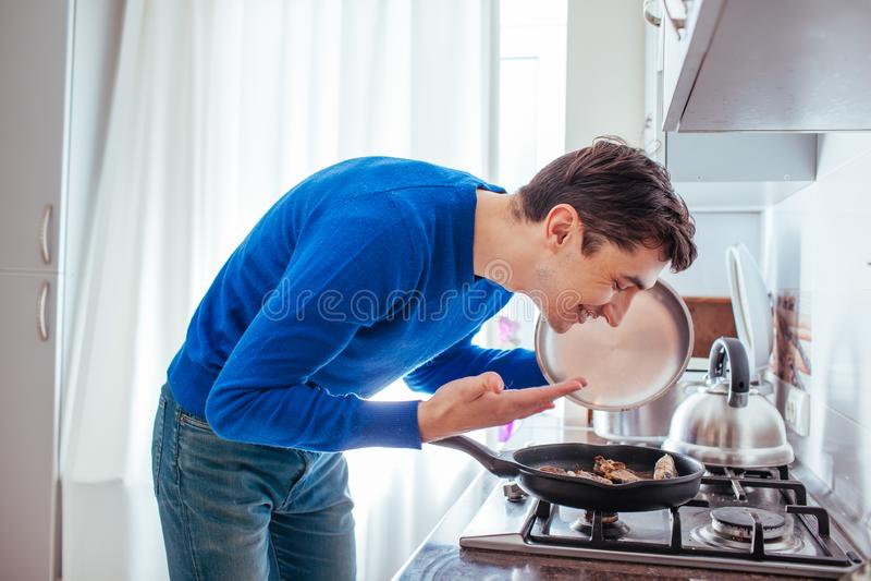 年轻人从平底锅的嗅食物 免版税图库摄影