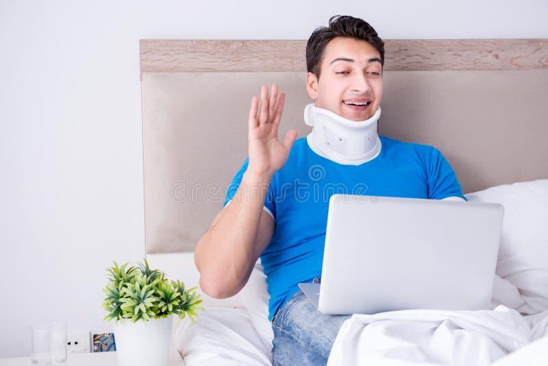年轻人以脖子伤在床上 库存照片