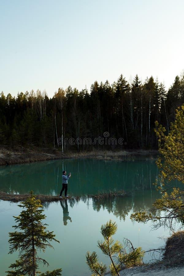 年轻人作为旅行照片-拉脱维亚- Meditirenian样式的美丽的绿松石湖颜色在波罗的海国家- 免版税库存照片