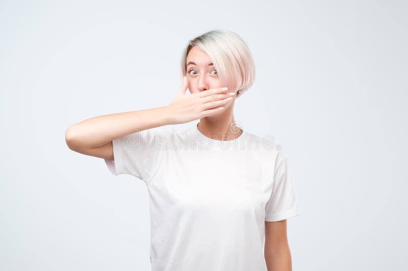 年轻人使有短的色的头发覆盖物嘴的妇女惊奇用她的站立反对灰色背景的手 图库摄影