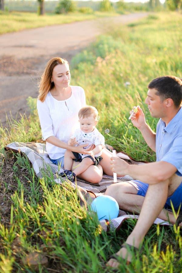 年轻人使sittling在与一点婴孩和吹的泡影的草的父母欢喜 免版税图库摄影