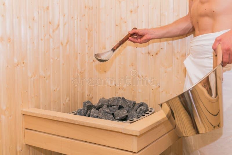 年轻人倾吐水入热的石头在蒸汽浴温泉室 免版税库存图片