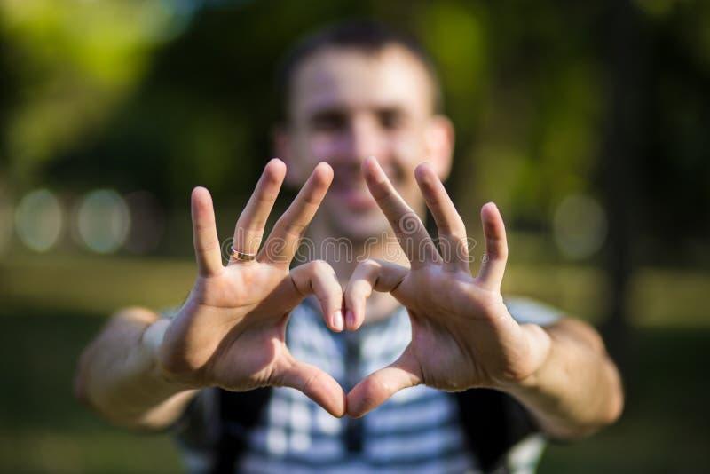 年轻人做在爱心脏形状的手  免版税库存照片
