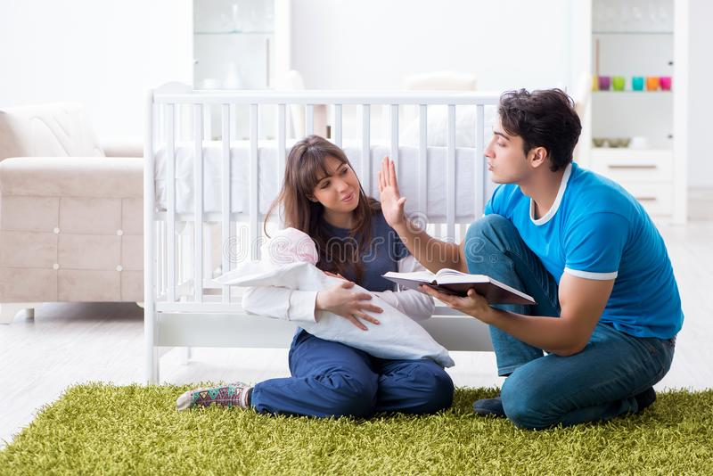 年轻人做父母与他们新出生的婴孩坐地毯 库存照片