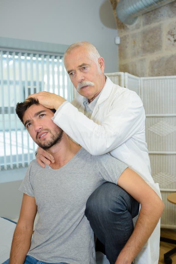 年轻人做舒展与生理治疗师的锻炼 库存图片