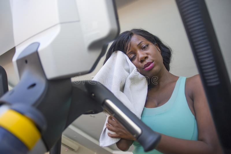 年轻人健身俱乐部干燥的被用尽的黑人美国黑人的妇女冒汗了疲乏和满身是汗的训练省略机器坚硬锻炼 免版税图库摄影