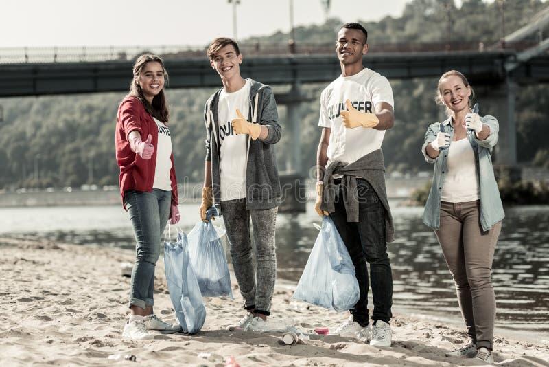 年轻人公司志愿提高他们的与他们的团队负责人的赞许 免版税库存图片