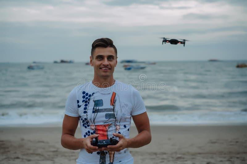 年轻人发射在海洋的quadrocopter 休息和冒险与寄生虫 人` s玩具 免版税库存照片