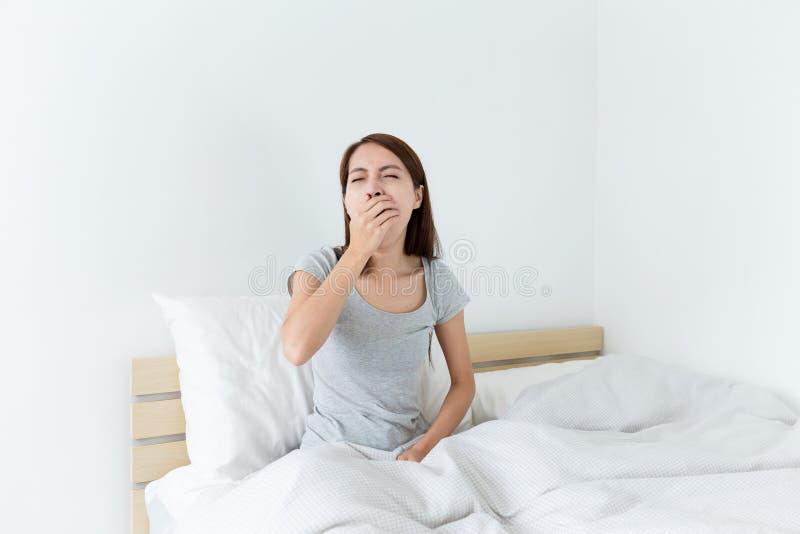 年轻人叫醒打呵欠,并且手包括她的嘴 库存照片