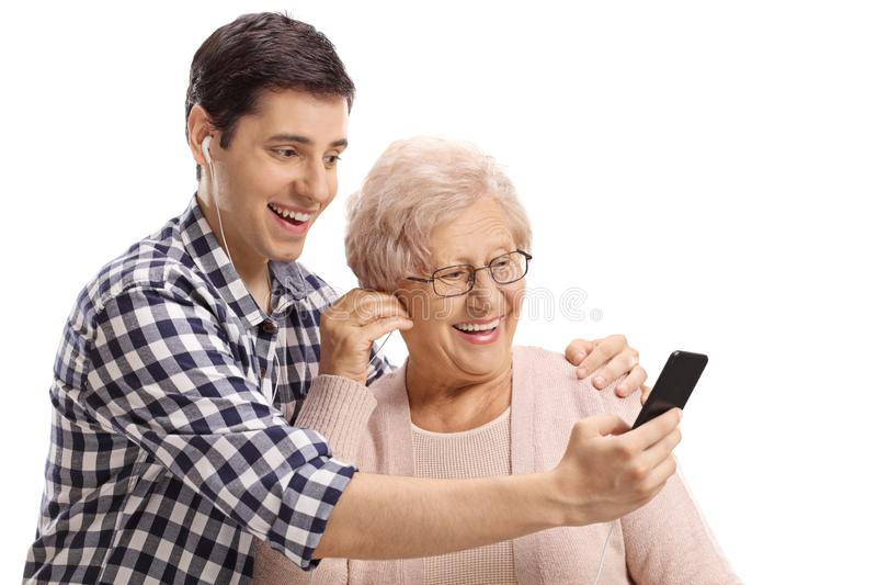 年轻人和听到在智能手机的音乐的一名资深妇女 免版税库存图片