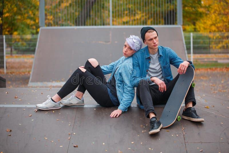 年轻人和女孩溜冰板者,户外在一明亮的秋天天 免版税库存照片