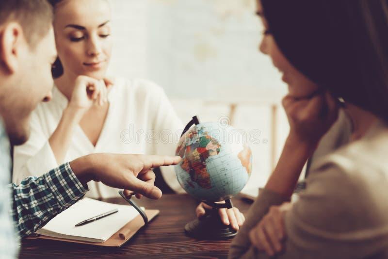 年轻人和妇女在旅行社中与经理 免版税库存照片