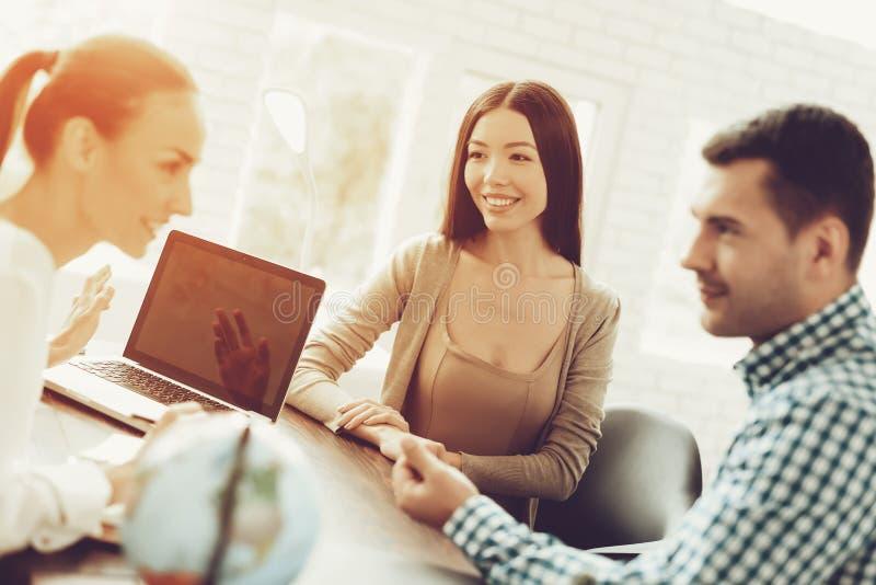 年轻人和妇女在旅行社中与经理 免版税库存图片