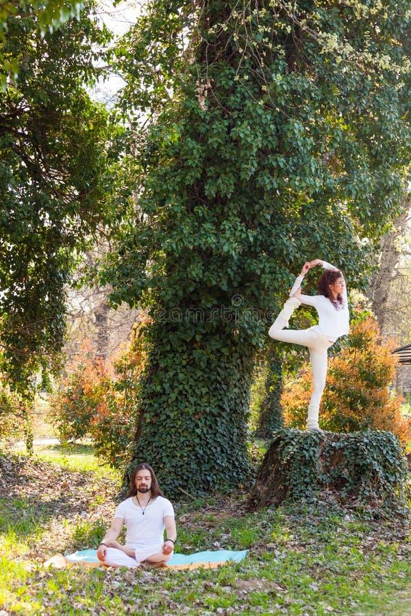 年轻人和妇女实践瑜伽室外在木夏日 库存图片