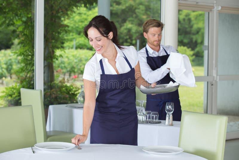 年轻人和妇女承办酒席服务的在餐馆 免版税库存图片
