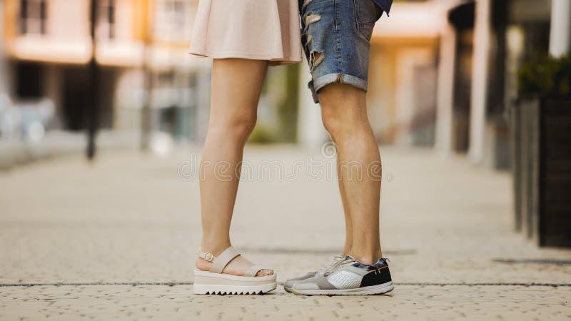 年轻人和妇女站立接近彼此的,浪漫关系的腿 免版税图库摄影