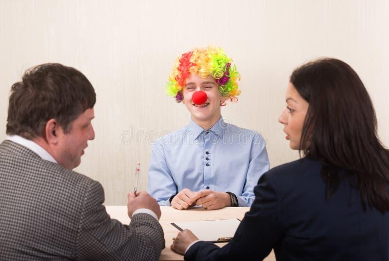年轻人和成员滑稽的画象在工作面试中的  免版税库存照片