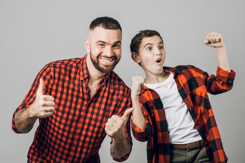 年轻人和男孩时髦的红色被检查的衬衣的高兴在喜讯 免版税库存图片