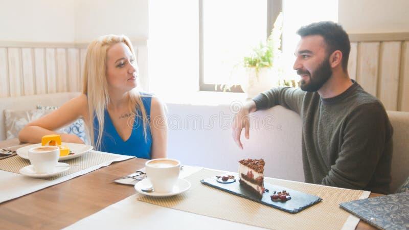 年轻人和白肤金发的妇女采取咖啡在咖啡馆 免版税库存照片