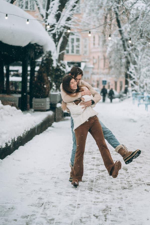 年轻人和美女获得在一条多雪的街道上的乐趣 在毛线衣的夫妇 图库摄影