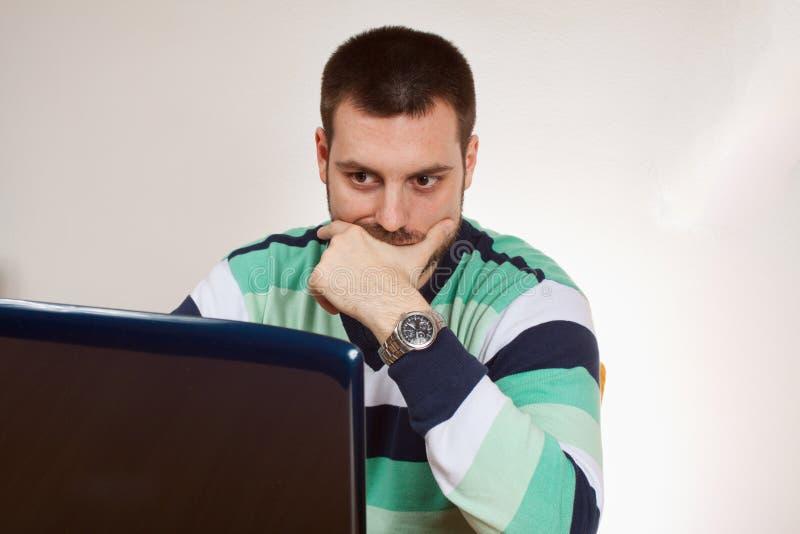 年轻人和膝上型计算机 免版税库存照片