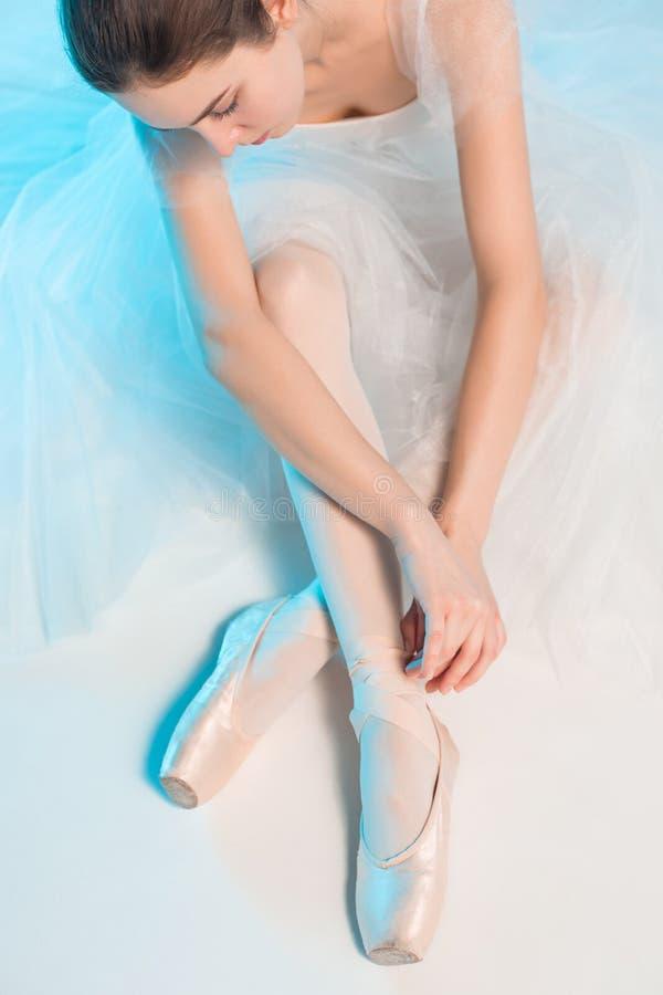 年轻人和难以置信地美丽的芭蕾舞女演员在一个蓝色演播室坐 免版税库存照片