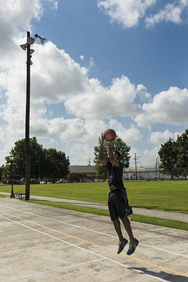 年轻人在一个街道法院的训练篮球在市新奥尔良,路易斯安那 库存照片