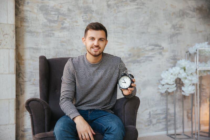 年轻人在他的手上坐椅子并且拿着一个时钟 对stant的时间 帅哥微笑和等待的合适时候 免版税库存图片