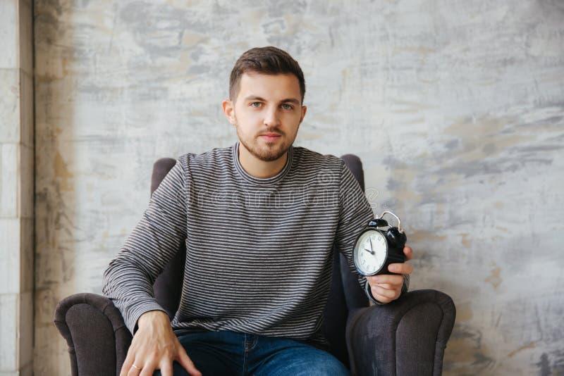 年轻人在他的手上坐椅子并且拿着一个时钟 对stant的时间 帅哥微笑和等待的合适时候 库存照片