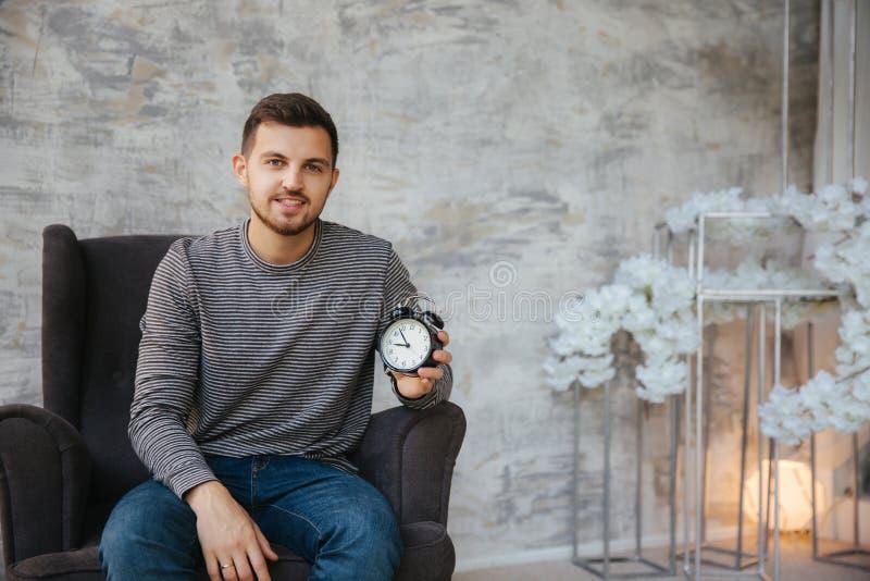 年轻人在他的手上坐椅子并且拿着一个时钟 对stant的时间 帅哥微笑和等待的合适时候 免版税库存照片