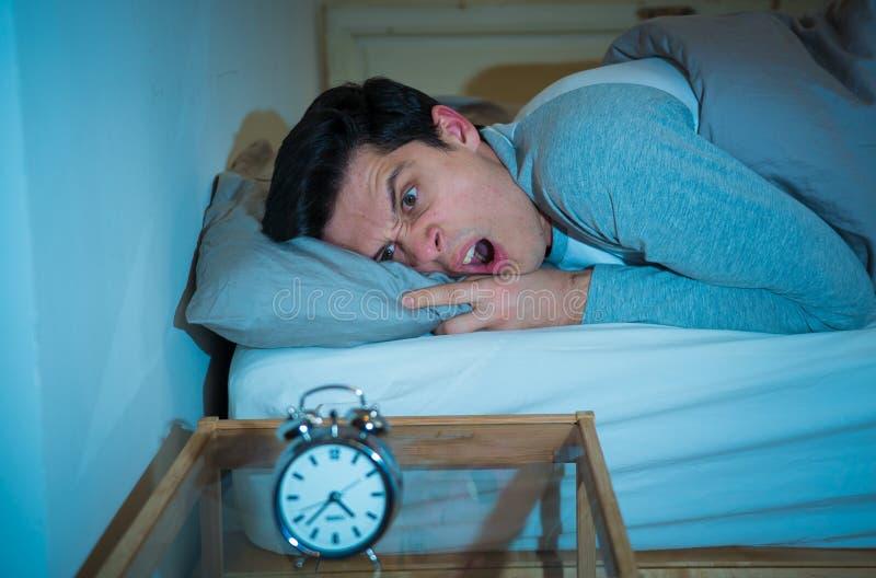 年轻人在充满绝望闹钟不能的感觉和的困厄的床上睡觉以失眠 库存照片
