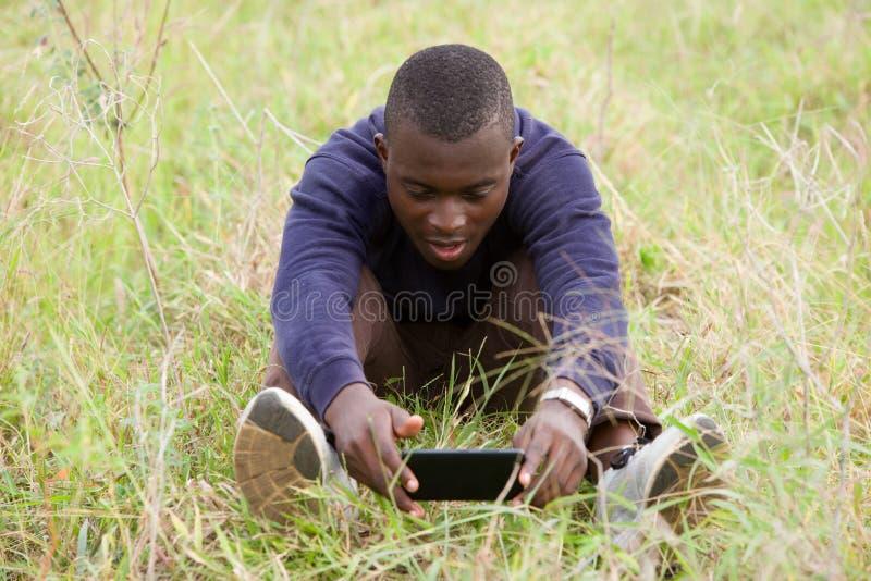 年轻人在公园使用一个手机 库存照片