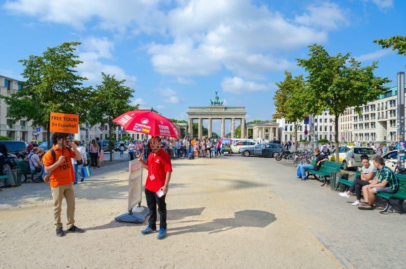 年轻人在勃兰登堡门,柏林,德国附近提供被引导的游览用西班牙语 免版税图库摄影