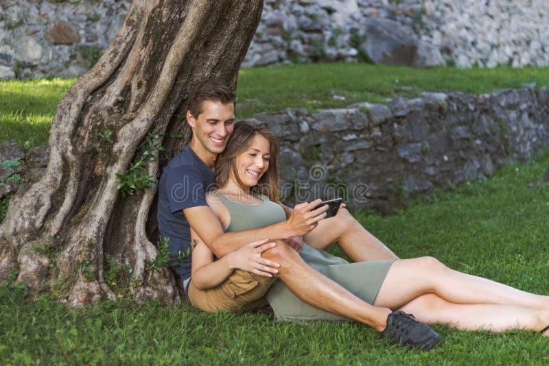 年轻人在坐在城堡的一棵树下的爱结合 库存照片