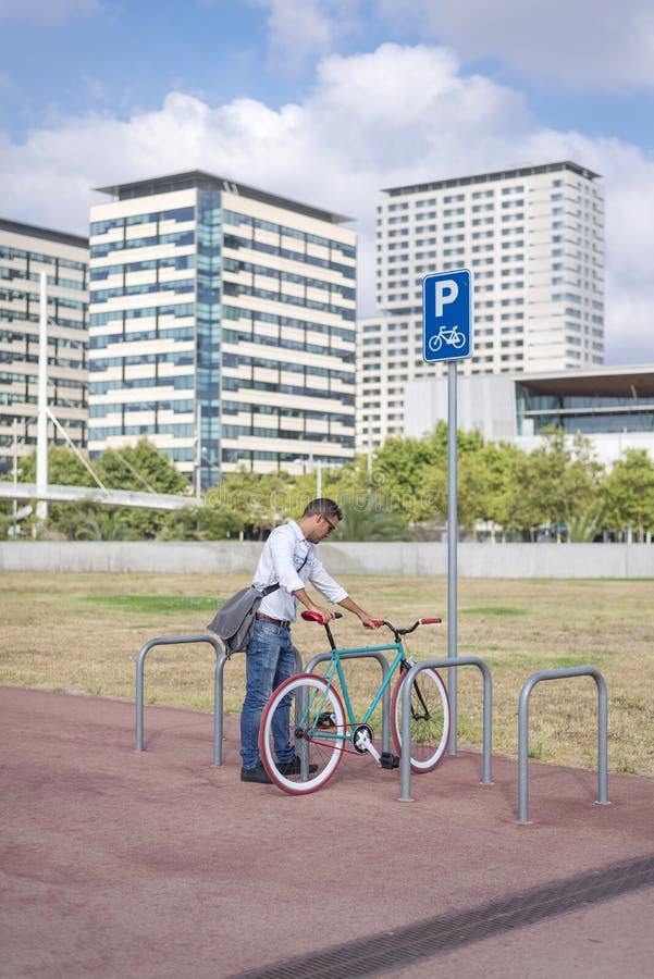 年轻人在城市街道上的停车处自行车 库存照片