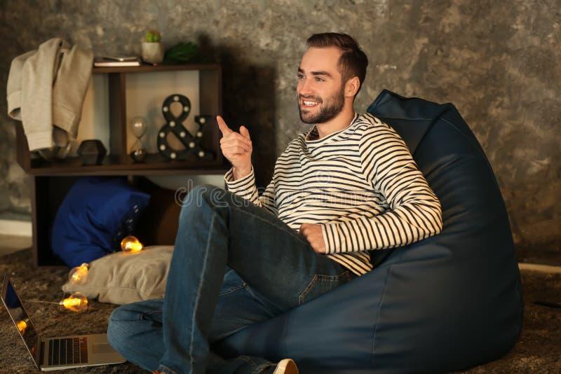 年轻人在家坐装豆子小布袋椅子 免版税库存图片