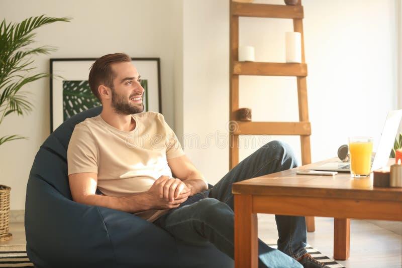 年轻人在家坐装豆子小布袋椅子 免版税库存照片